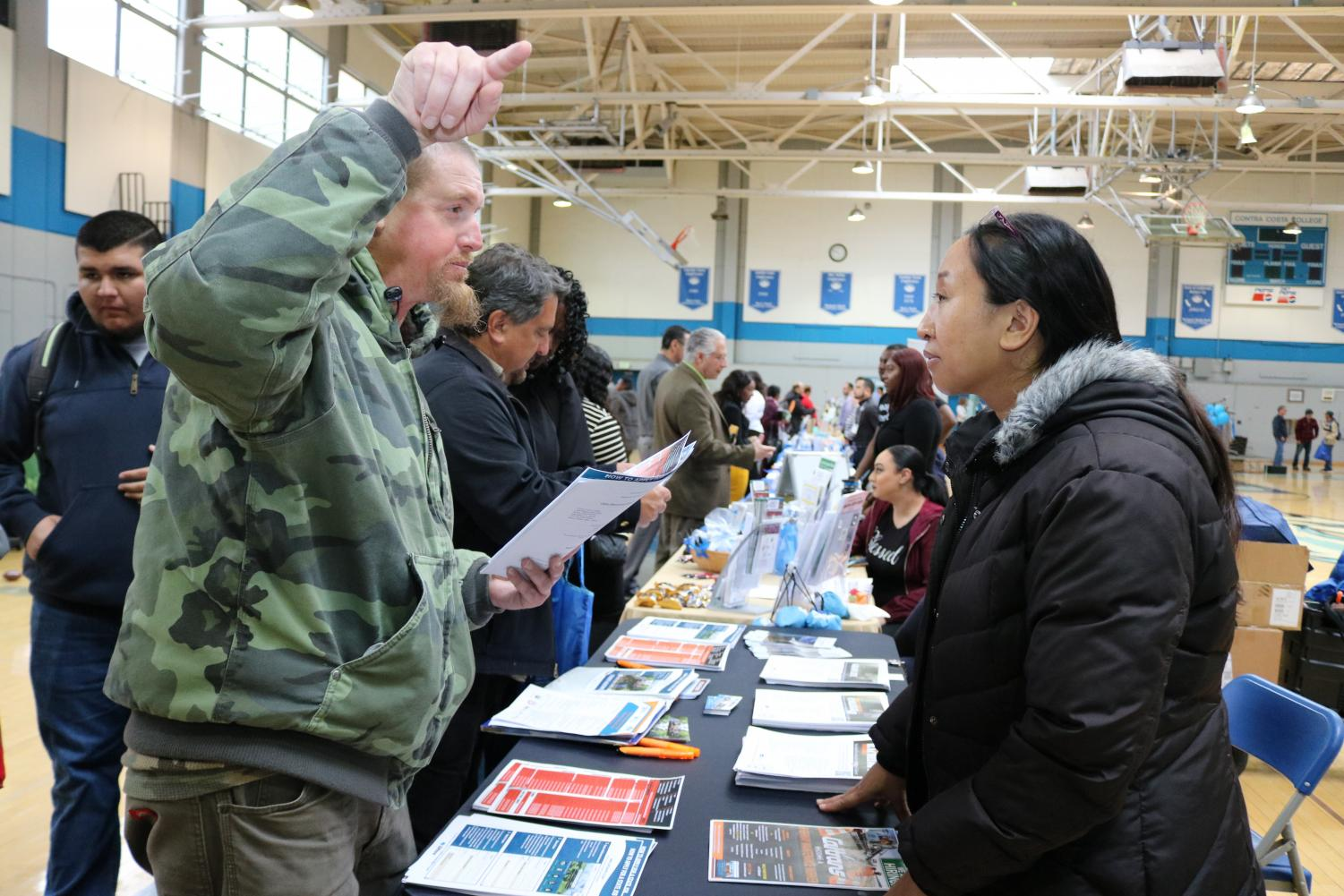 A student (left) talks to CalTrans representative, who refused to give her name, during the West Contra Costa County job fair on March 20 in the Gymnasium. More than 50 employers and 20 resource tables were available for students to explore.
