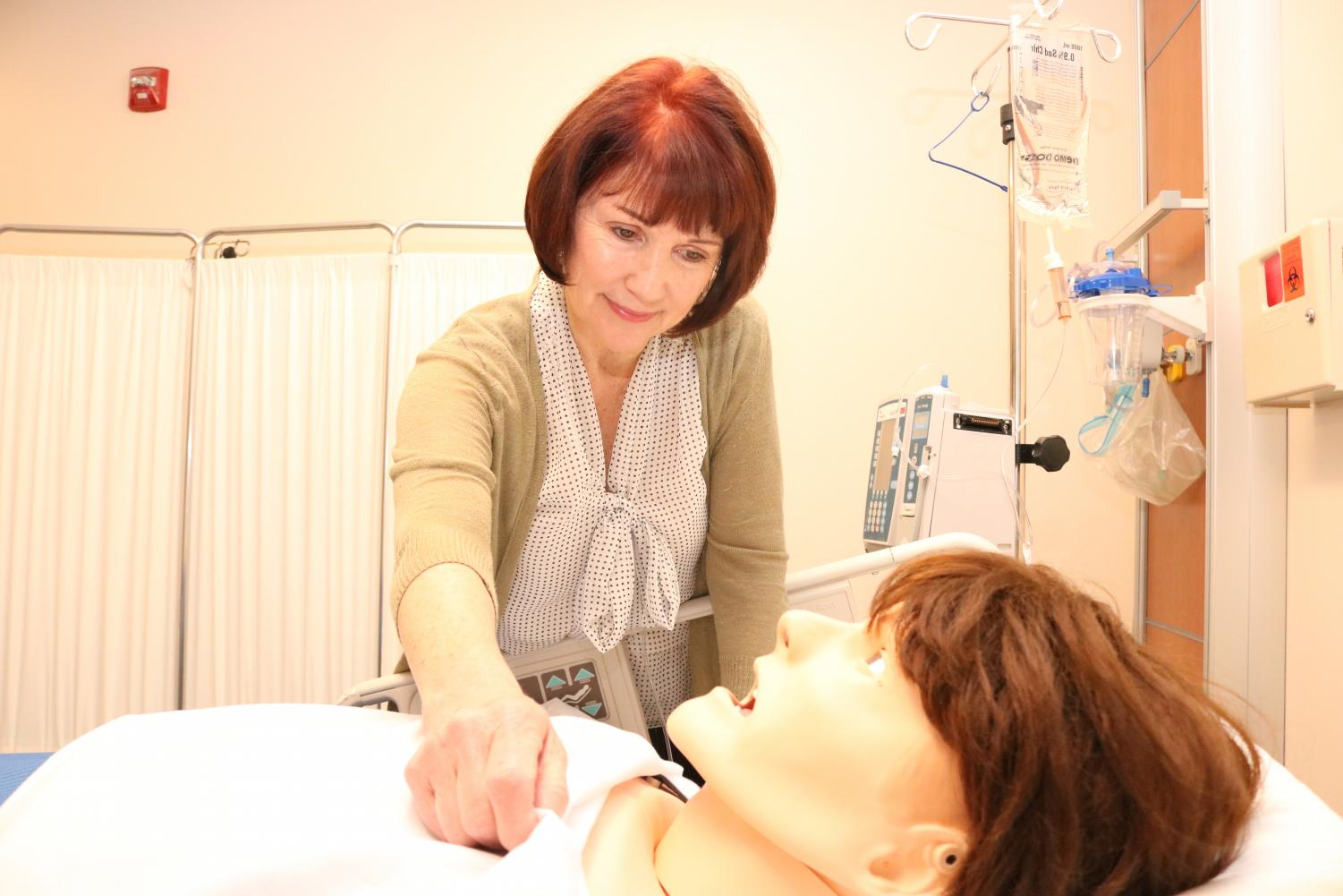 Dr. Cheri Etheredge  cares for a simulation  mannequin in the Simulation Lab in the Applied Art Building.  Etheredge has been  teaching in Contra Costa College's nursing department  for 38 years.  This semester she was awarded the district's Teacher of the Year award.
