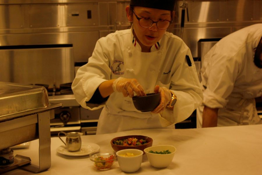 Culinary arts major Pei Niee Chuah prepares a bowl of vegan sweet potato soup with coconut milk and decorates it with cilantro, corn and broccoli during the Empty Bowls event on Friday.