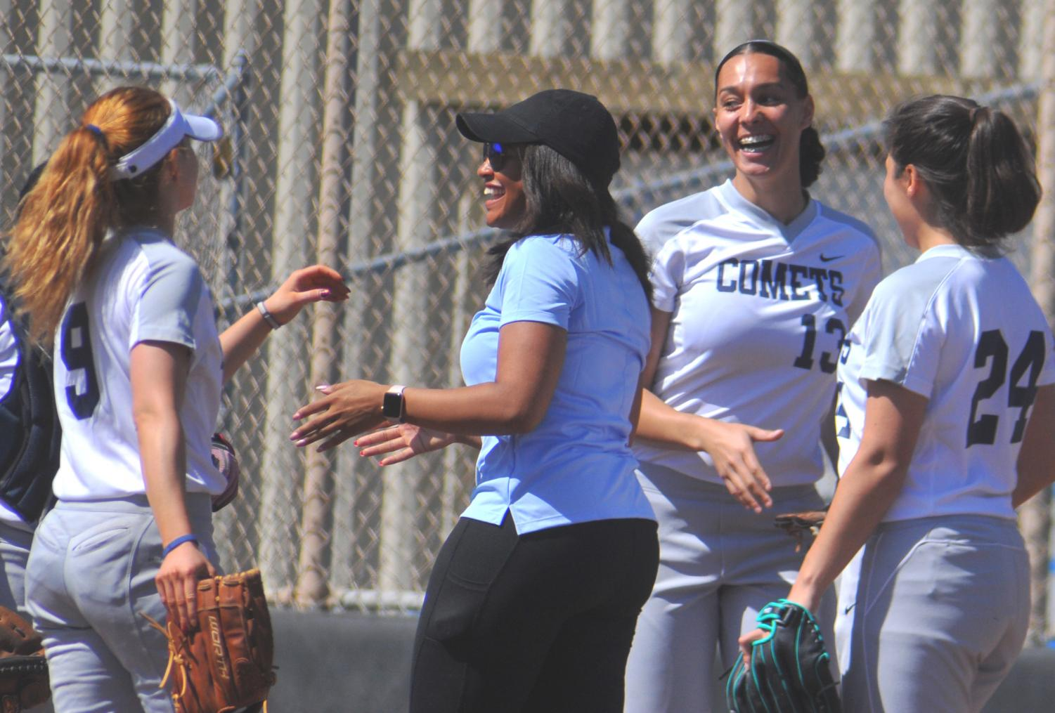 Coach Taylor Harris (middle) has adjusted the way the softball team is coached because of the level the team is at. Harris has coached a seasoned team before, and now takes up the challenge to start off with an inexperienced squad.