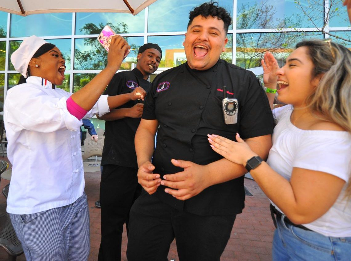 Culinary arts major Robin Jassa (middle right), Kassane Clay (left), Brandon Williams (middle left) and Elizabeth Razo, celebrate Jassa as he wins a scholarship for a trip to Italy at the Food and Wine event on Sunday.