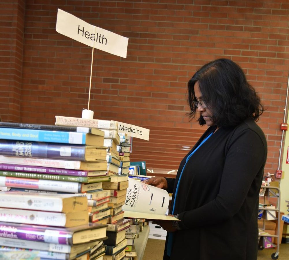 Friends of The Library volunteer Michelle Naidoo arranges books in Contra Costa College Library during its Annual Book Sale on May 7.