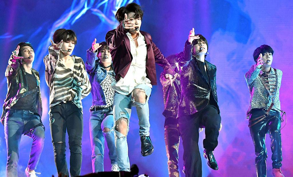 BTS performs a choreographed group dance routine and sings during one of its concerts.