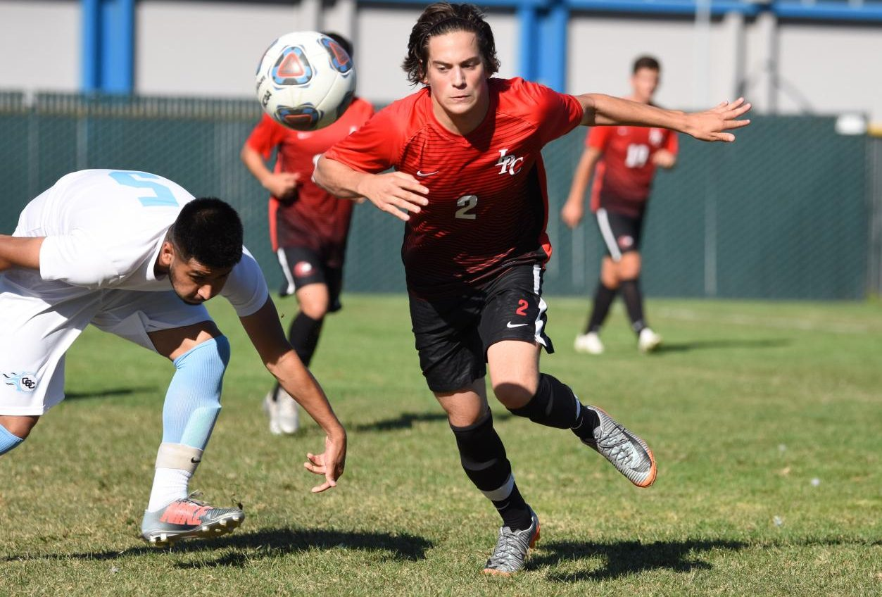 A Las Positas player runs for a bouncing ball as he passes a Comet player during Contra Costa College's 2-0 loss on Sept. 17 at the Soccer  Field.