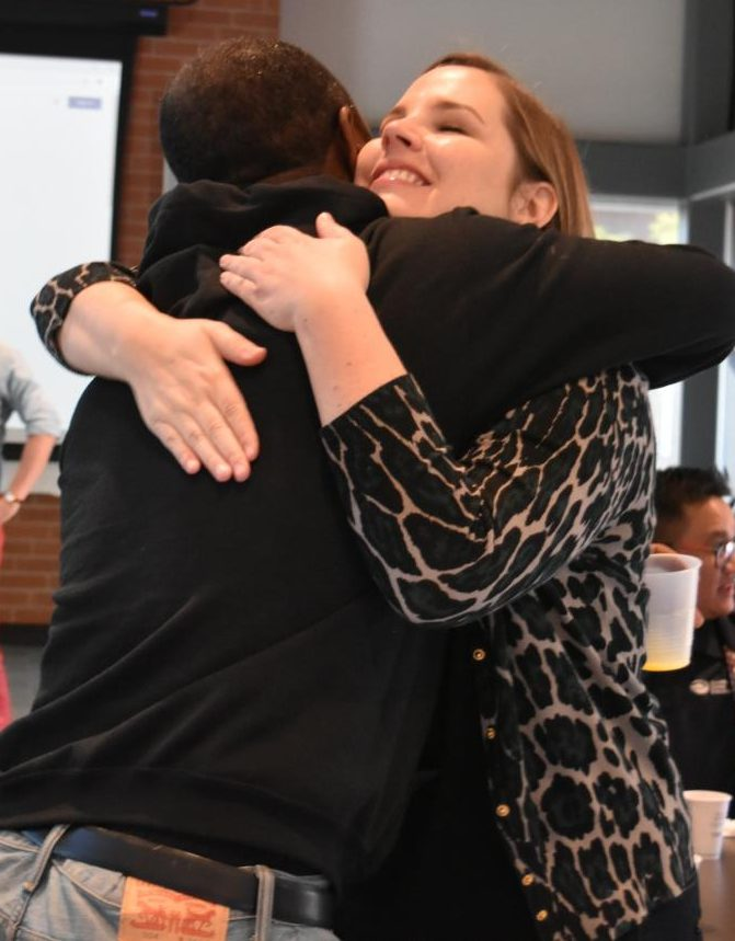 EOPS/Care CalWORKs Manager George Mills hugs Brandy Howard (right) during a brunch and ceremony in Fireside Hall on Oct. 11.