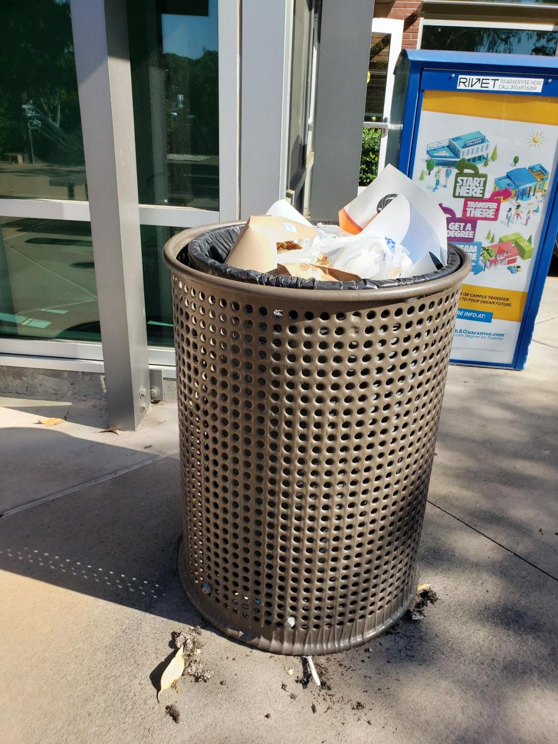 A trash can near the Student Services Center is filled to the brim with garbage due to significant custodial worker and equipment shortages on campus leaving some areas on campus unattended.