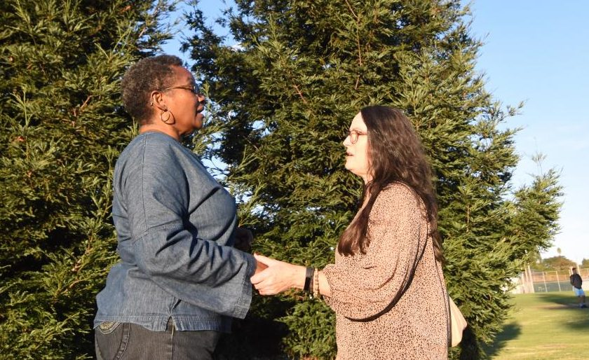 Kristine Kilian Lobos (right) shakes hands and greets a new friend on campus on Oct. 4.