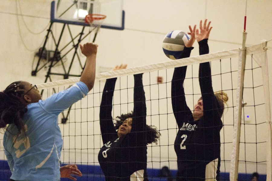 Freshman middle blocker Christina Hall (left) hits the ball past two defenders during the Comets' game against College of Alameda on Oct. 16 at Pinole Middle School.