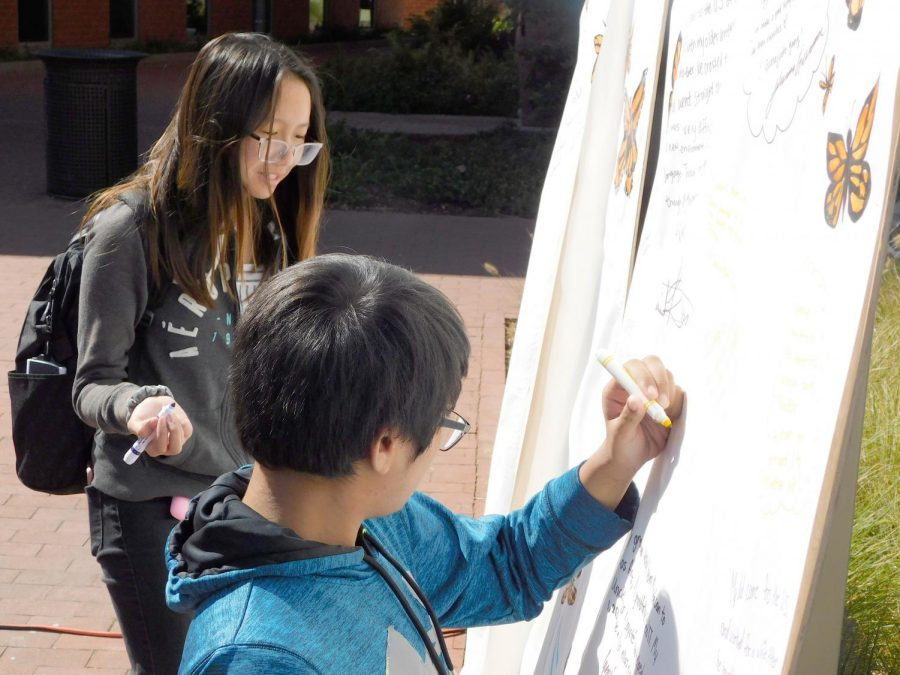 Students write messages on a poster during the annual Undocum- ented Student Week of Action in the Campus Center Plaza on Oct. 14.