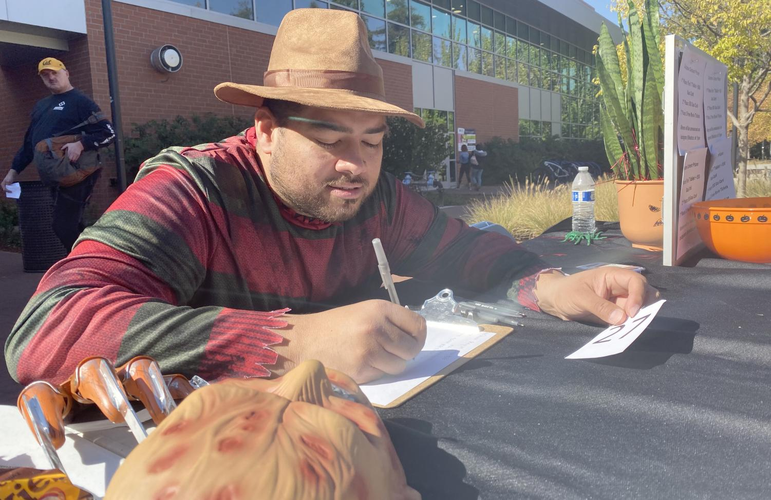 Student Life Coordinator Charles Ramirez assigns numbers to the participants in the Halloween costume contest in the Campus Center Plaza on Oct. 30.