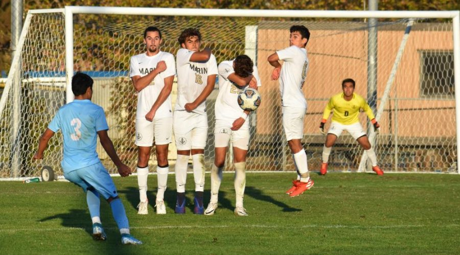 Freshman midfielder Christian Diaz (left) takes a direct free kick during Friday's 4-0 loss to College of Marin.