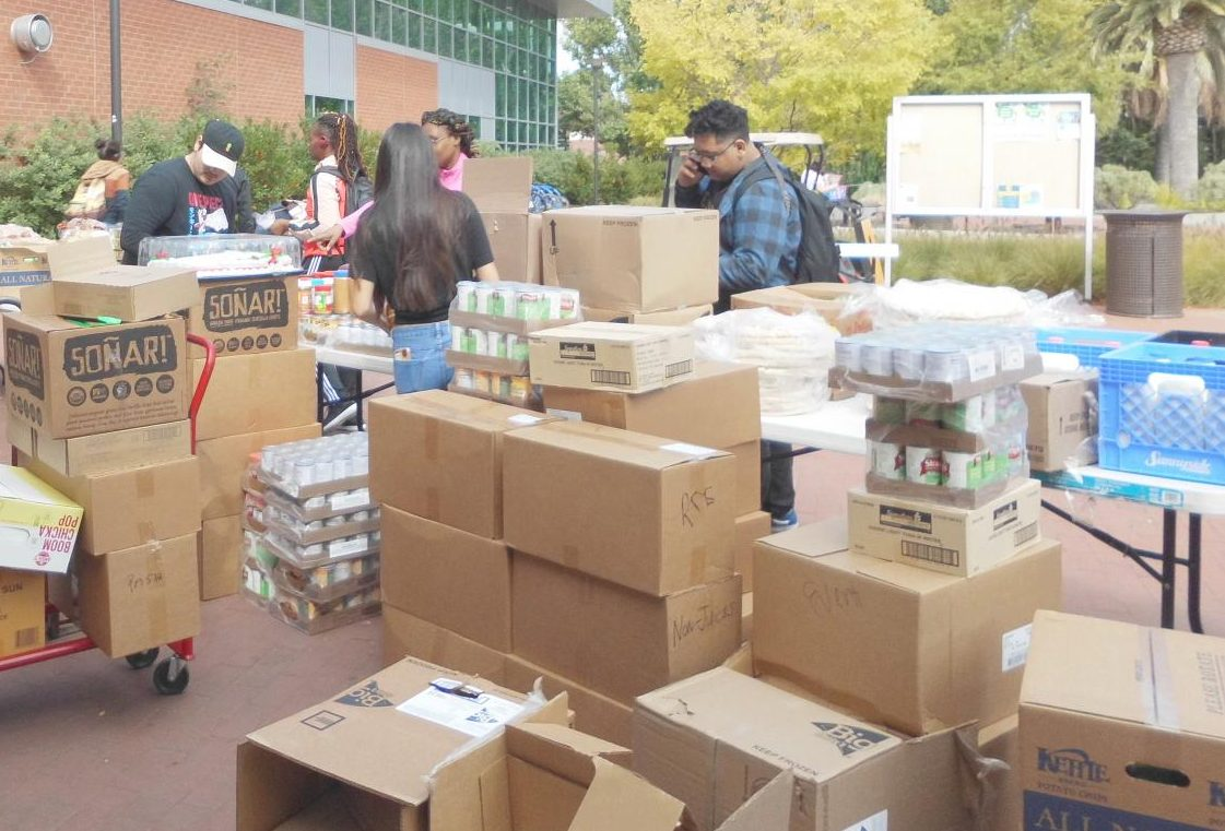 Students gather around a newly arrived shipment of food for the campus Food Pantry and begin unpacking it and take it to SA-234, where it is stored.