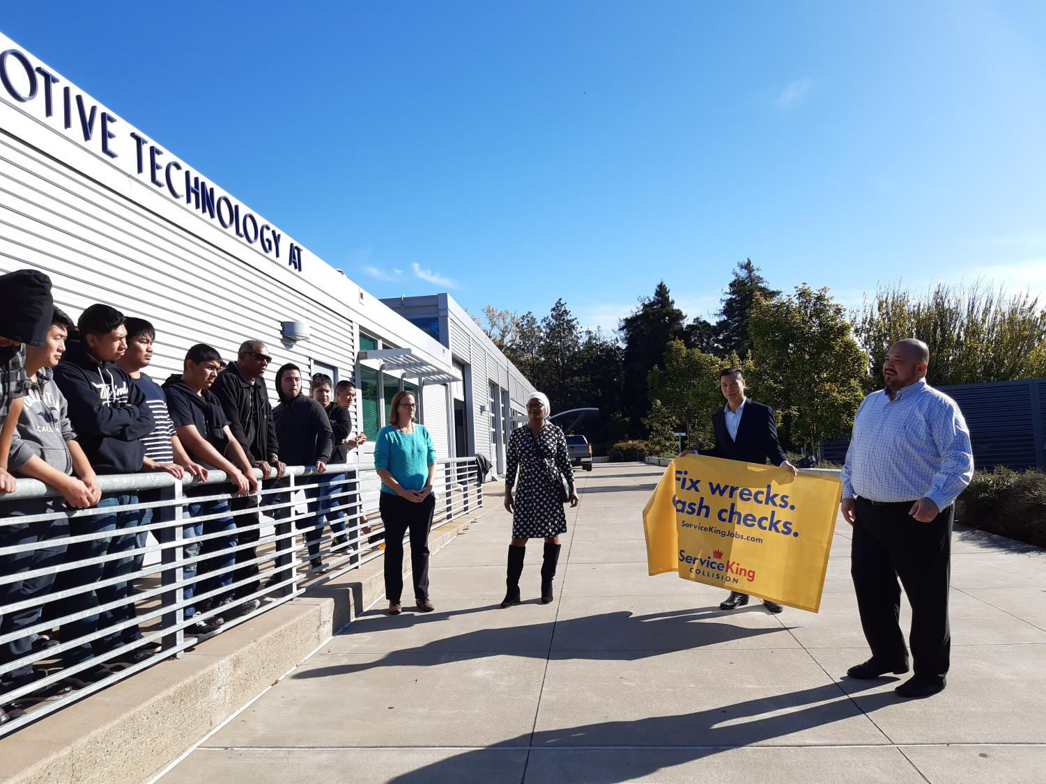 Roy Villarreal, learning program director of Service King Collision Repair (far right), speaks words of advice to collision repair students at a ceremony where he presented a $5,000 check to the CCC automotive department on Dec. 3.