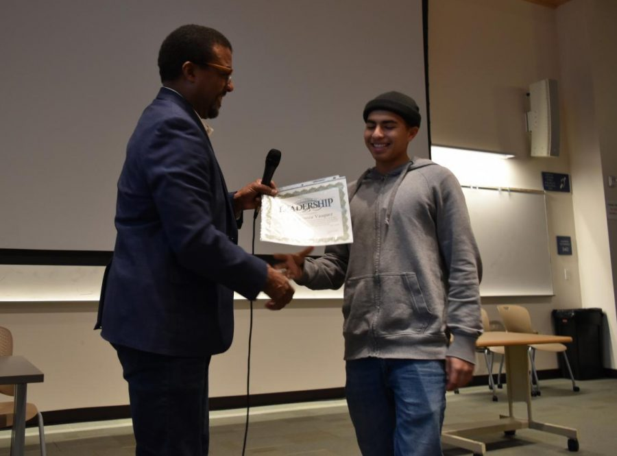 Gateway to College Director Karl Debro presents a leadership award to Gateway student Angel Espinoza Vasquez during an annual awards ceremony