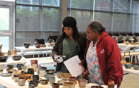 Contra Costa College students admire ceramic plates created by ceramics students in Fireside Hall on Thursday during the annual Ceramics Sale.