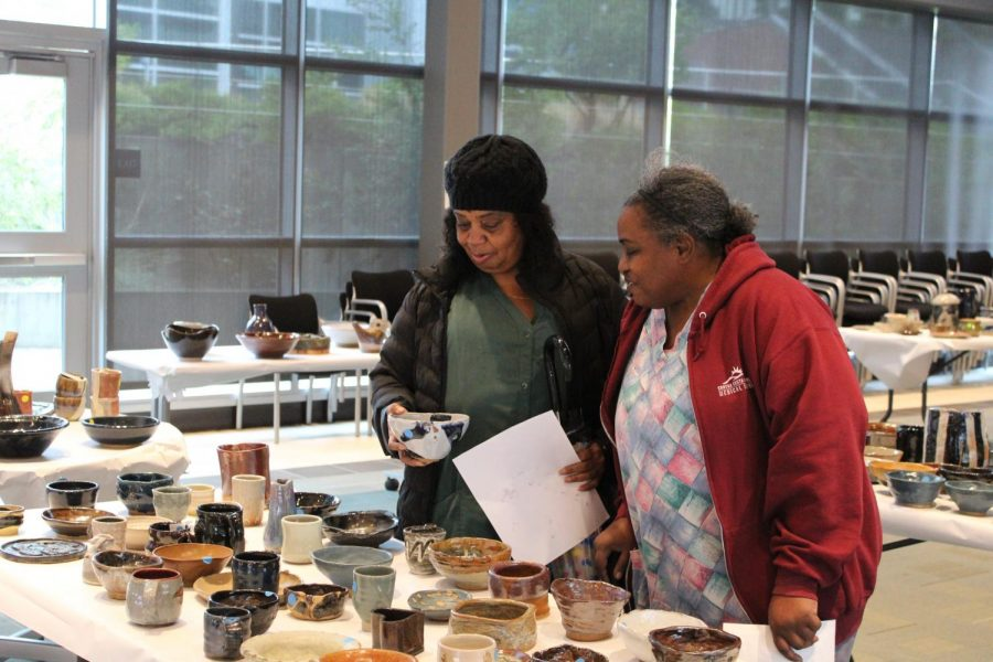 Contra+Costa+College+students+admire+ceramic+plates+created+by+ceramics+students+in+Fireside+Hall+on+Thursday+during+the+annual+Ceramics+Sale.