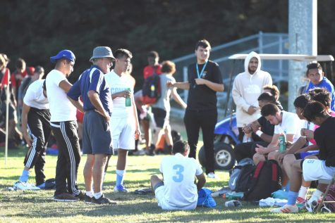Former  men's soccer  coach Rudy Zeller  (left middle) places his hands on his hips as the squad sits on their bench during a game this season. Zeller ended his term as coach at halftime during a game against Napa Valley on Oct. 4.