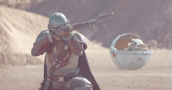 "The Mandalorian (Pedro Pascal) aims his cycler rifle with Baby Yoda by his side during the new Disney+ original series ""The Mandalorian."""