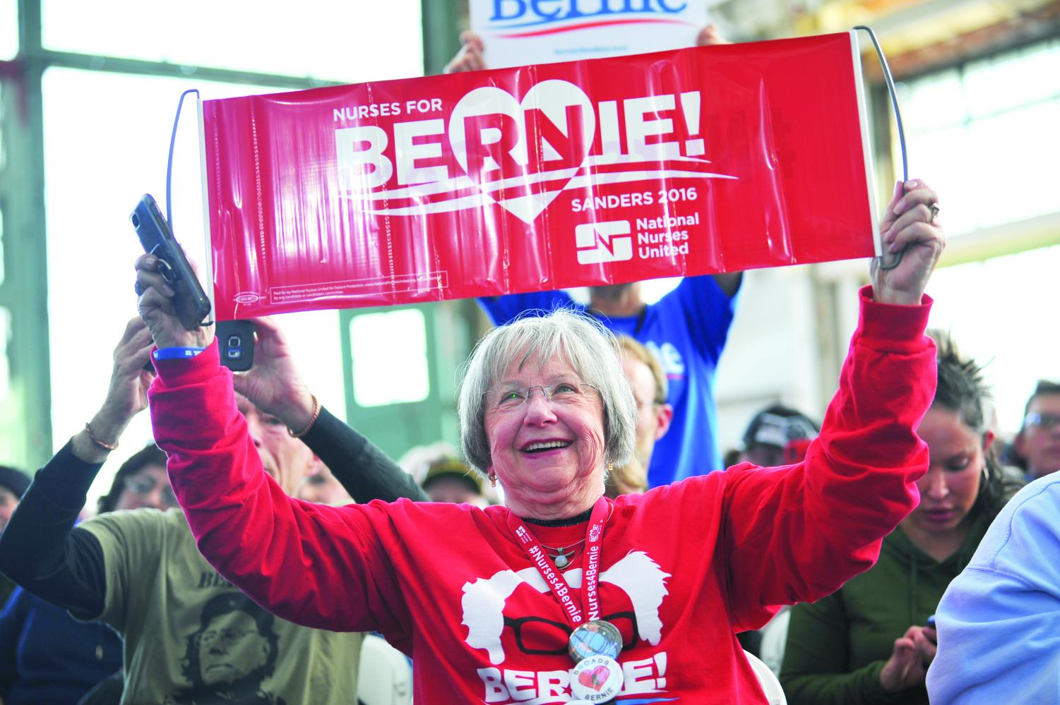 An+attendee+holds+up+a+2016+Sanders+campaign+sign+reading+%E2%80%9CNurses+for+Bernie%E2%80%9D+during+a+rally+at+Richmond%E2%80%99s+Craneway+Pavilion+on+Monday.+%0ASanders%E2%80%99+campaign+policies+have+not+changed+much+from+his+2016+campaign%2C+and+have+been+adopted+by+many+of+his+democratic+rivals.+