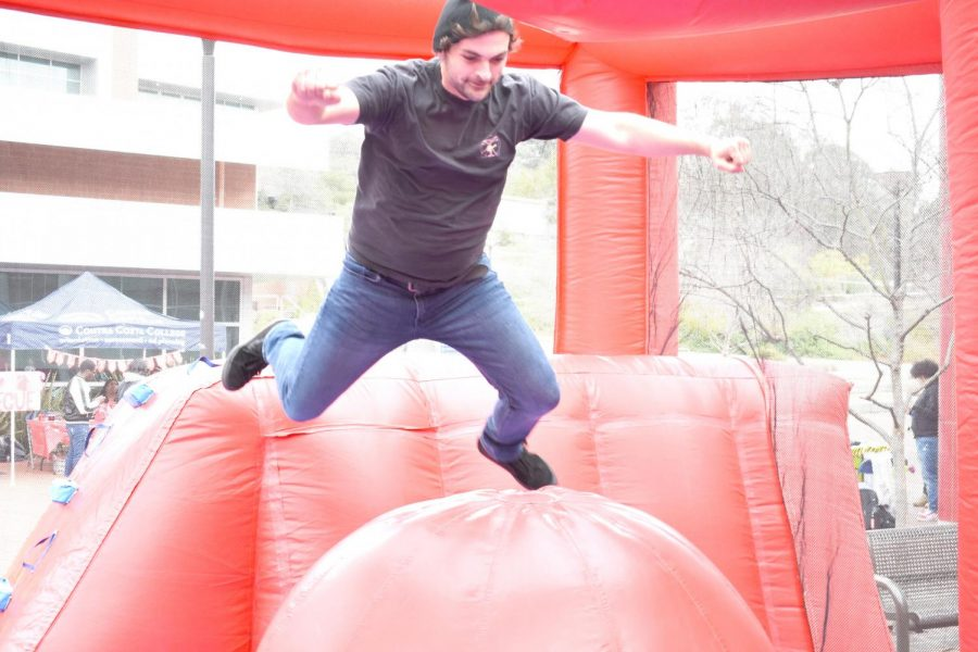 "Contra Costa College student Brandon James attempts to finish the obstacle  challenge, based on the TV show ""Wipe Out,"" during Club Rush, held in Campus Center Plaza on Thursday."