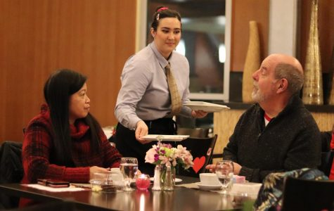A waiter serves community members Madeleine and James Machado at the Cupid's Season Dinner Scholarship Event on Friday.