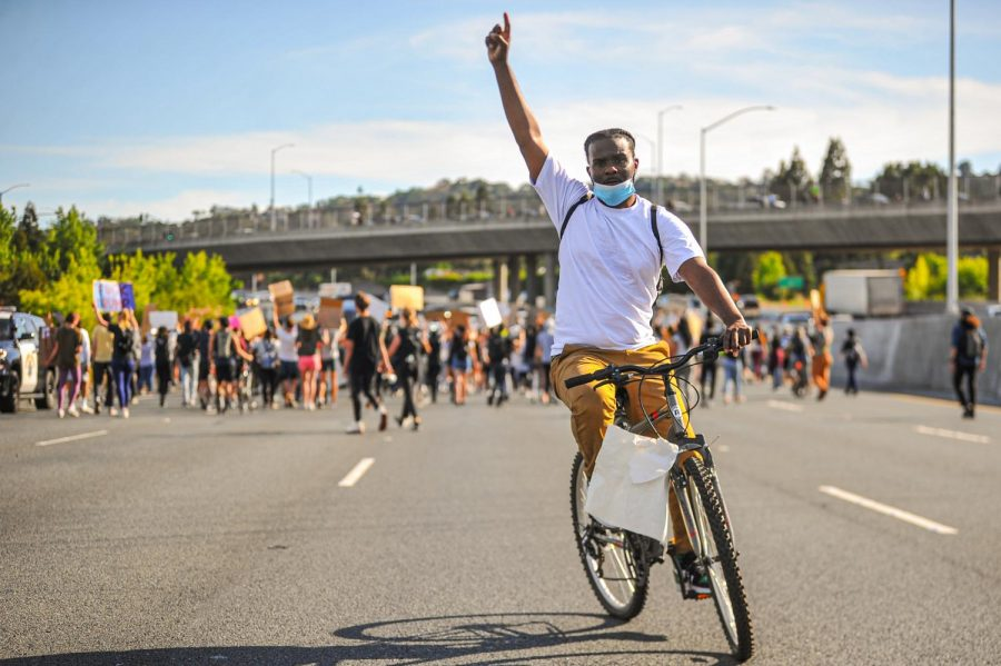 San Francisco resident Dav Gerald raises his hand in the air as he cruises on northbound Interstate 680 lanes shut down in Walnut Creek, California on June. Gerald is not part of any particular organization, but has been participating in any protest he can attend.