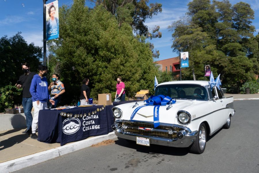 On May 6, Honors student Angelina Padilla receives her grad pack at the drop-off zone in her familys 1957 Chevrolet, decorated with flags and a big bow. (From left to right) Larry Womack, David De La Cruz, Jason Cifra, Dennis Franco and Kate Weinstein distribute grad packs to students .